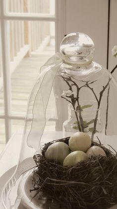 Spring Decorating from larasheleheda.com.  Sweet and simple...nest, eggs and glass cloche.