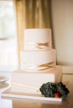 Three-Tiered White Cake with Gold Details. Cakes by Gina, a Houston-based baker, created this three-tiered white wedding cake. A square base topped with two round tiers is adorned with simple gold stripes for a clean yet modern look. A cost-saving secret? The cake decorative dessert was a faux-cake, save for the one tier the couple cut. Guests enjoyed slices of sheet cake, but no one knew the difference.