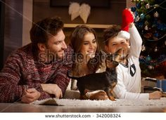 Happy young family enjoying playing with new puppy at christmas.