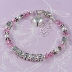 Child Name Bracelet - C10   This brand new design features Swarovski crystals and pearls with Bali sterling silver. Little hearts are featured either side of the name.   This picture shows the C10 design with heart lobster clasp and puff heart charm - small letter blocks. Crystal colour - light rose. Pearl colour - white.
