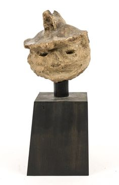 Japanese (possibly Kofun period, circa 250-600 A.D.) Haniwa soldier head raised on a later tapered black wood base. Figural head with carved almond form eyes and wearing hat, nose broken off. Sculptural head likely originally from Iyo Shikoku.