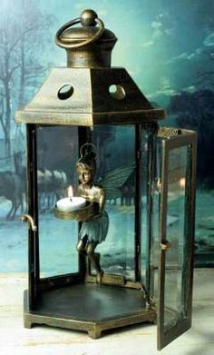 """Tinkerbell Fairy Lantern A notion conjured from the beloved tale of Peter Pan, the dangling sprite bears light that darts from within the glass as she swirls upon a chain. Aluminum/glass. Bronze/verdigris finish. 16""""."""