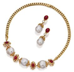 CULTURED PEARL, RUBY AND DIAMOND DEMI-PARURE, VAN CLEEF & ARPELS.  Comprising: a necklace set at the front with three cultured pearls capped to each side by foliate diamond set motifs, alternating with stylised clusters of cabochon rubies and brilliant-cut diamonds, the back of flat curb linking, unsigned, maker's marks,  together with a pair of pendant ear clips of matching design, signed Van Cleef & Arpels NY