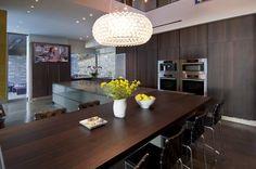sleek modern kitchen with dark wood cabinets, wall ovens, hidden pantry door