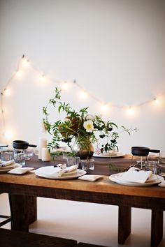 A simple string of party lights with candles & a loose floral arrangement