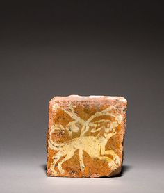 Running dog France, Burgundy (?) Late 14th century 10 x 10.5 x 2 cm; two-colour earthenware tile, white slip on pale pink firing body, lead glaze