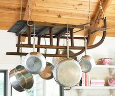 LOVE IT! Would look so neat in a cabin.  Repurposed Pot Rack  Start imagining new purposes for old things and you'll find new storage solutions. Here an antique sled becomes a pot rack when suspended from the ceiling. It provides a handy place to hang pots and pans while adding flea market style to the space.
