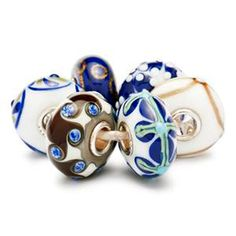 334022-64608-Trollbeads Blue Christmas Kit - Limited edition. In this beautiful blue kit we celebrate Christmas with flowers and decorative ornaments. And with lots of gold dust in midnight blue glass - sparkling as the stars in the clear Christmas sky.