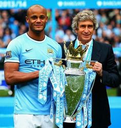 May 11, 2014: Manchester City's captain Vincent Kompany and manager Manuel Pellegrini hold the English Premier League trophy.