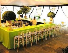 "A communal square bar acts as the perfect ""centerpiece"" for the reception space making a fun visual statement with lime green draping, large green topiaries in white urns and a row of white bamboo stools."