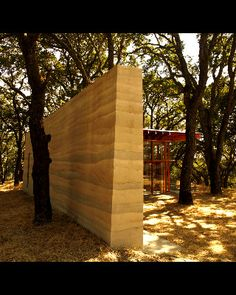 rammed earth walls inspired by the stratified colors of the rock outcroppings of…
