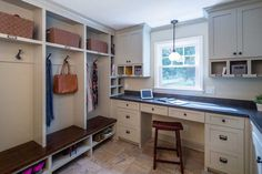 Mudroom features a wall of built in open lockers, one for each individual family member, boasting labeled cubbies filled with woven baskets stacked over lockers lined with oil-rubbed bronze hooks and bench fitted with shoe shelves.