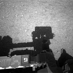 This is the first image taken by the Navigation cameras on NASA's Curiosity rover. It shows the shadow of the rover's now-upright mast in the center, and the arm's shadow at left. The arm itself can be seen in the foreground. Image released Aug. 8, 2012.