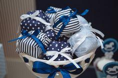 Os bem-nascidos oferecidos aos convidados do chá de bebê foram embrulhados em tecidos com padronagens diferentes, mas com as cores escolhidas pela futura mãe para a comemoração: azul marinho, azul claro e branco