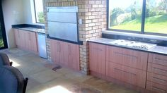 Created by Dimension Cabinets - Indoor braai area with cupboard and drawer space in Memphis Cherry melamine and Rustenburg granite tops.