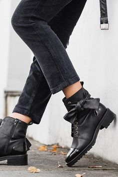 Black Flat Ankle Boots.  Add a statement finish to skinny jeans with Kurt Geiger London's black Daze boot. This lace-up style is punctuated with style nods from its tonal patent toe cap to its oversized bow addition that adds a subtly feminine slant.