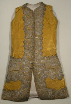 Waistcoat, 1750-1760, made from gold silk damask lined with cream twilled silk facings and part lining with a cream linen back. It is trimmed with silver lace 10cm deep around the front and the hem and round and on the pocket flaps. The lace is made en disposition. There are 17 buttons embroidered with silver purl and plate.