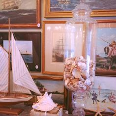 large glass bottle with shells, water-themed art work, toy boat: available for purchase at Uncommon Market Dallas, 100 Riveredge Drive, Dallas, Texas 75207; call us @ 214-871-2775 if you would like to put this item on a 2 day HOLD.