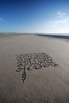 South African calligrapher Andrew van der Merwe has developed various wedge- and scoop-shaped tools to allow him to carve letters out of beach sand. This is a picture of one of his creations, on a beach in Belgium.