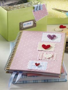 Fotoalbum-Rohling (Bastelladen)buntes Papier (Bastelladen)Motivscheren (Bastelladen)doppelseitiges Klebeband (z. B. von Tesa)Herzen