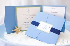 Anchors aweigh. This light blue pocket-fold invitation is accented with navy blue and celery green colors to create a nautical and preppy look. The anchor design on the monogram tag is carried throughout the invitation. Photo credit: JLowe Photos