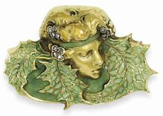 Lalique 1900 'Leafed Woman' Brooch:  diamonds and enamel on gold in the form of a female head with headband of enveloping leaves.