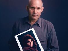 Famous photographers holding their most iconic or favorite photos. Photographer Steve McCurry with his photo of Sharbat Gula