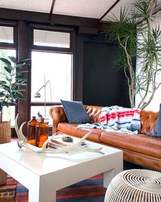 Higgins Chesterfield sofa in caramel leather, Stan floor lamp, and kilim rugs in our midcentury / boho living room. Couch and lamp made in the USA by Roger + Chris.