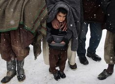 photo by Musadeq Sadeq of a boy waiting with others for winter clothing in an Afghan IDP camp.