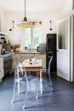 Cuisine avec table ancienne et une suspension à l'esprit récup et des chaises transparentes trés modernes