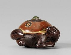 A lacquered wood netsuke of a water kettle changing into a tanuki, by Yûsô. 19th century.  Illustrating the fairy tale 'Bunbuku chagama, the head and bushy tail of the badger turned sideways to form a compact shape. The chagama lacquered brown, the knob of the lid green, details heightened with makie; the himotôshi lined with green stained bone. Signed Yûsô with kaô on a red lacquer tablet.