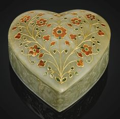 A MUGHAL HEART-SHAPED JADE BOX SET WITH GEMSTONES, NORTH INDIA, 19TH CENTURY the jade shaped as a heart with a slightly domed cover, the sides finely carved in relief with leafy flowerheads and buds, the cover decorated in the kundan technique with large floral blossoms and colourful stones 12 by 12 by 5cm.