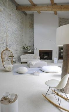 Dans une ancienne grange restaurée en salon une belle couleur gris perle met en avant le mur de pierres apparentes. Les canapés et poufs blancs complètent l'ambiance douce et feutrée de ce salon.