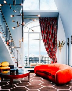 Gorgeous and bold living space with modern light fixture, red sofa, and tall ceilings