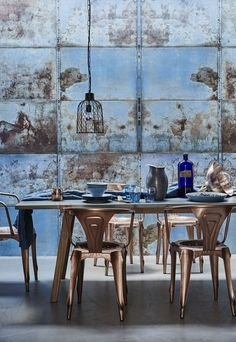 Distressed-effect wallpaper brings depth and drama while burnished metals such as copper and zinc evoke the industrial beauty of seagoing vessels. Find more dining room ideas at housebeautiful.co.uk