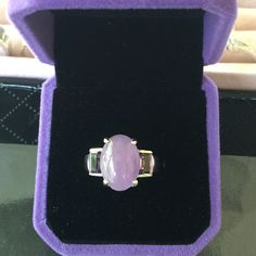 Beautiful Genuine Amethyst Ring Set in Sterling silverhas a large raw oval amethyst in the center with an emerald shaped amethyst on east sidethis is a size 7.25 and is in new conditionit is Hallmarked 925 with a designer mark Jewelry Rings