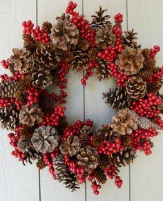 Corona navideña hecha con piñas de pino de diferentes tamaños y colores, entrelazadas con arándanos rojos deshidratados.