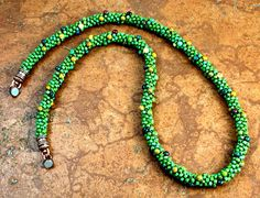 Ever seen the desert in bloom? Its one of my favorite memories from childhood and inspired the design of this necklace. Ranging from wine to tan, black, blue, and green, a multi-hued palette of earth tone beads spirals around this turquoise green necklace. Each bead has a picasso finish,