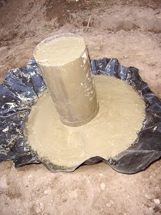 DIY Cement Mushrooms:  The crown is created by digging a hole in the ground and filling with cement, the stem is a two-liter drink bottle with its top and bottom lopped off.
