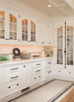 Love the curve topping glass front kitchen cabinets