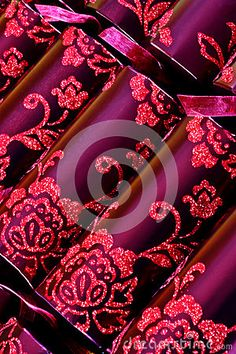 Background of luxurious purple Christmas crackers with pink floral design.