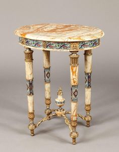 Constructed in Algerian Onyx, bronze and with champlevé enamel panels; rising from turned and tapering legs with toupie feet, having a serpentine conjoining stretcher issuing from the central flambeaux capped baluster form urn; the apron having running panels of champlevé enamel interspersed with paterae; the elliptical top with a moulded edge. French, Circa 1875