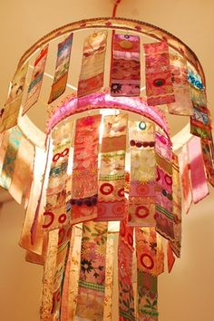 a handmade three tier chandelier made from strips of handmade paper and embellishes with buttons, beads and other embelishments