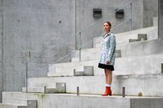 Danish Fashion and Style blogger Marie Jensen from NEMESIS, BABE blog wearing green, printed oversize second hand mens shirt, black, pleated short black second hand skirt, white socks, red heeled second hand boots, charlotte lebeck  spike earrings, wrap finger ring and slicked back hair in a pony tail.  Trying out a bigger silhouette with feminine touches.