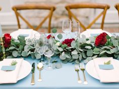 Pale blue tablescape accented with foliage and bold red flowers | http://www.stylemepretty.com/2015/02/06/romantic-cranberry-dusty-blue-wedding-inspiration/
