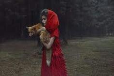 Ik weet niet wie deze foto heeft gemaakt, maar ik zelf heb er een roodkapje idee bij, alleen houd ze een vos vast inplaats van dat een wolf haar achtervolgd.  Voorstelling/concept,  je ziet een meisje in een rode mantel die een vos in haar armen houdt op een, zo te zien, open plek in het bos. Vormgeving, het meisje met de vos valt erg op, niet omdat ze op de voorgrond staat maar, omdat ze een rode mantel draagt, en de vos zelf rood/oranje is, en de achtergrond redelijk donker is. Techniek…