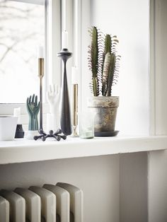 Windowsill decorations: a cactus, sculptures and candle lights.