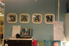 Maak creatief je naam met kleine fotolijstjes, zwarte letters en op de achtergrond leuk behang.