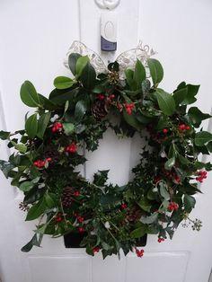 couronne de Noël originale en feuilles de houx, baies rouges et pommes de pin