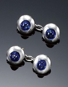 PAIR OF SAPPHIRE CUFFLINKS, 1920S. Each oval link applied to the centre with a cabochon sapphire, French assay marks.